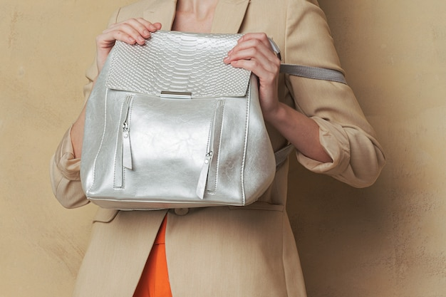 彼女の前に銀の革バックパックを保持している女性。