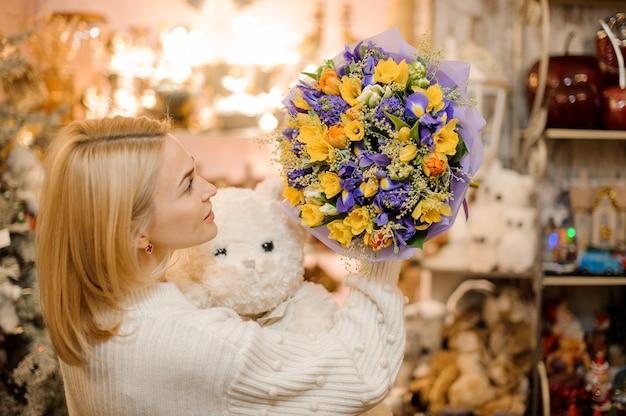 선물 종이에 싸서 보라색과 흰색 꽃과 작은 꽃다발을 들고 여자