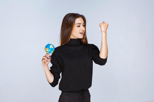 ミニ地球儀を持って拳を見せている女性。