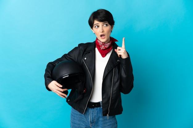 指を上に向けるアイデアを考えて青い背景で隔離のオートバイのヘルメットを保持している女性