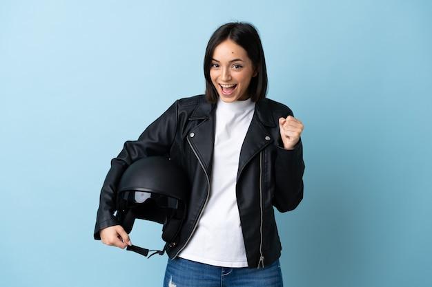勝者の位置での勝利を祝う青で隔離のオートバイのヘルメットを保持している女性