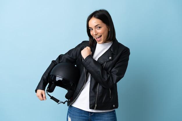 승리를 축하하는 파란색에 고립 된 오토바이 헬멧을 들고 여자