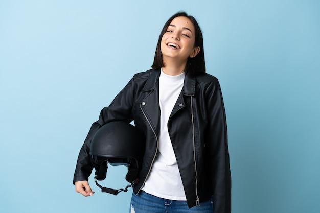 青い笑いで隔離のオートバイのヘルメットを保持している女性