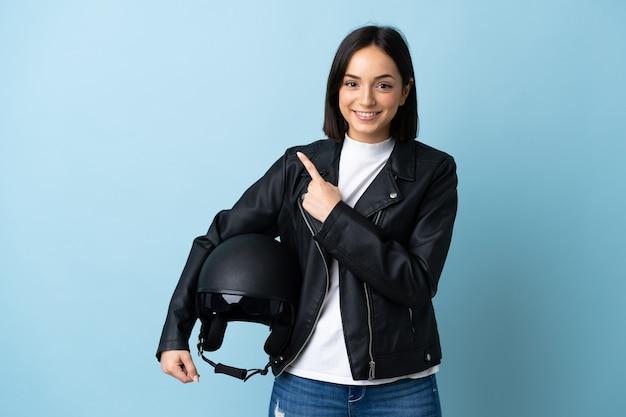 製品を提示する側を指している青で隔離のオートバイのヘルメットを保持している女性