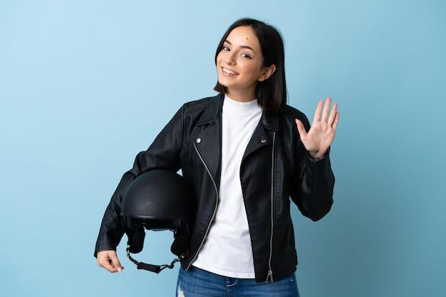 幸せな表情で手で敬礼の青で隔離のオートバイのヘルメットを保持している女性
