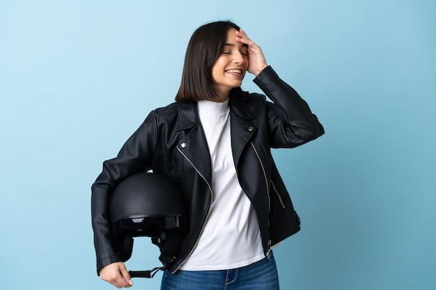 たくさん笑って青に分離されたオートバイのヘルメットを保持している女性