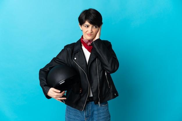 Женщина, держащая мотоциклетный шлем, изолирована на синем пространстве и закрывает уши