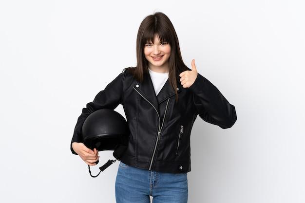 親指を立てるジェスチャーを与える白で隔離のオートバイのヘルメットを保持している女性
