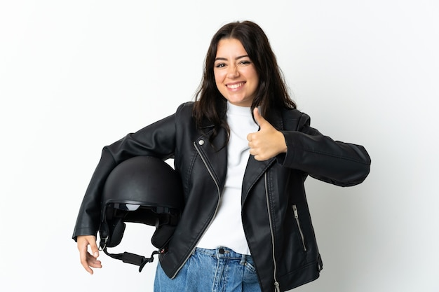 Женщина, держащая мотоциклетный шлем, изолирована на белой стене, показывая большой палец вверх
