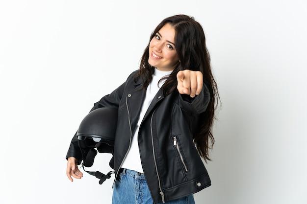 幸せな表情で正面を指して孤立したオートバイのヘルメットを保持している女性