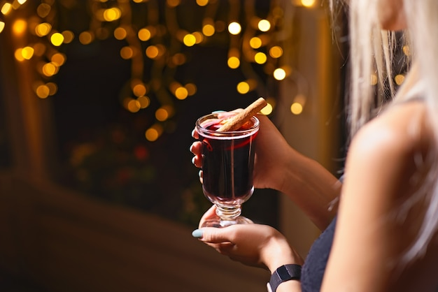 Женщина, держащая кружку горячего напитка глинтвейн. женские руки с чашкой сезонного горячего напитка. домашний горячий фруктовый чай