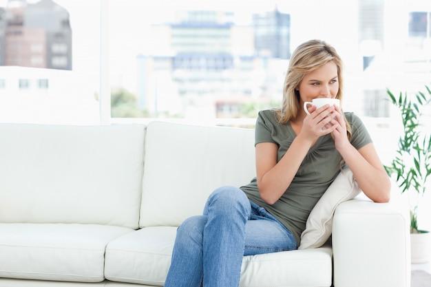 座っている間に彼女が横に見るように彼女は鼻にマグカップを保持している女性