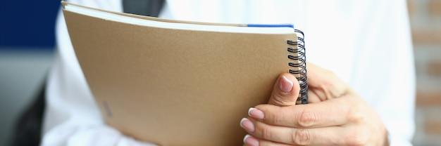 Женщина держит блокнот на пружине для экзаменов