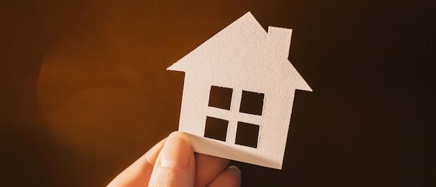 暗い表面にバックライトで彼女の手で紙の家を保持している女性