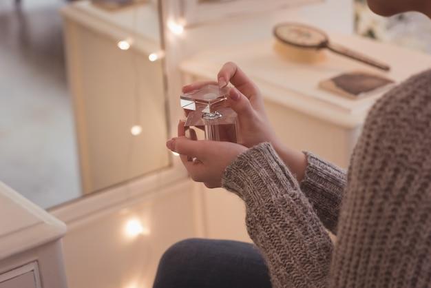自宅で香水瓶を保持している女性