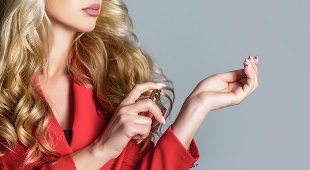香水瓶を持っている女性。女性は香水の香りを提示します。香水瓶を持つ女性。香水を使用している美しい少女。香水のボトルを持つ女性。香水瓶の女性スプレーアロマ。