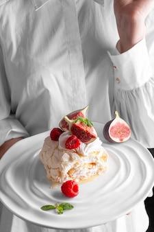 딸기와 무화과로 장식된 머랭 롤이 있는 돼지 접시를 들고 있는 여자