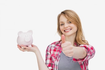 Woman holding a piggy bank with her thumb up