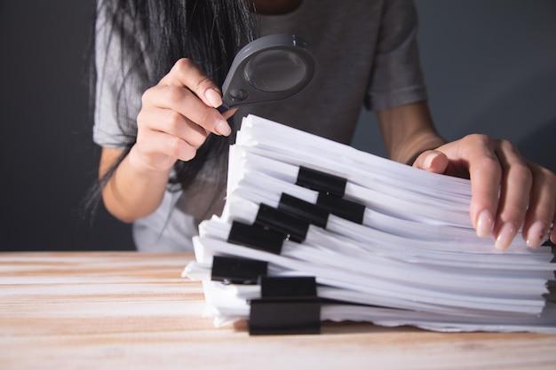 테이블에 서류 더미를 들고 여자입니다. 돋보기로 공부하다