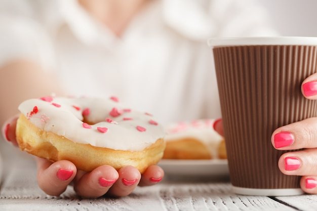 Женщина, держащая розовый пончик