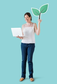Woman holding a plant icon and using a laptop
