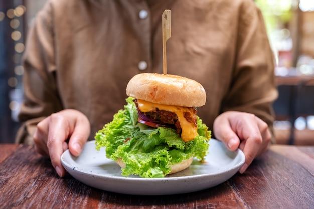 Женщина держит тарелку гамбургера из говядины на деревянном столе в ресторане