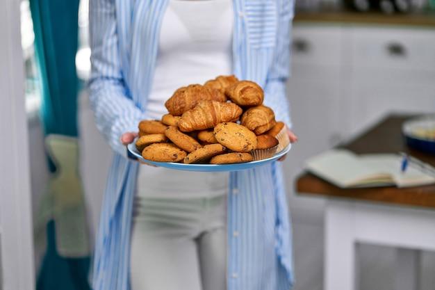 クロワッサンとクッキーのプレートを保持している女性