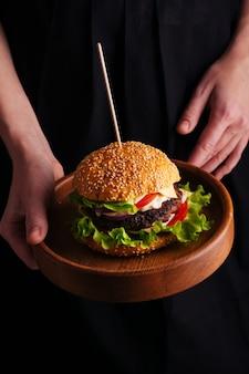 ハンバーガーとプレートを保持している女性