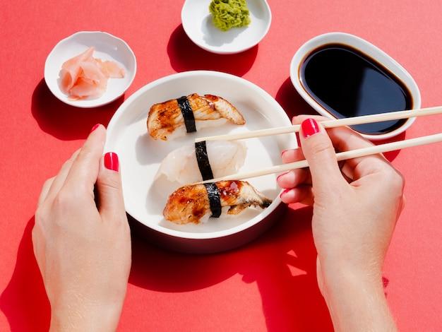 Женщина держит тарелку с суши