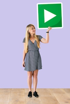 Женщина, держащая кнопку кнопки воспроизведения в студии