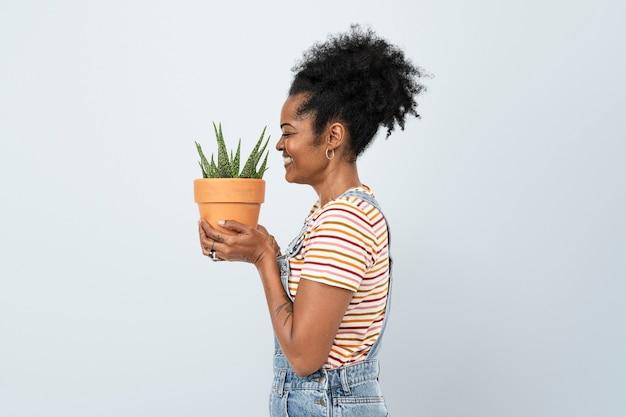 鉢植えのアロエベラ多肉植物を保持している女性