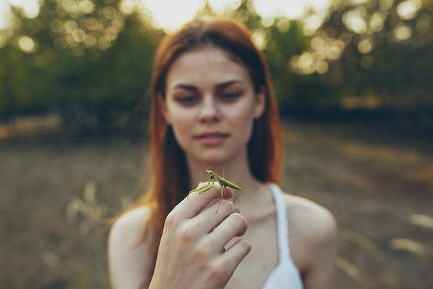 カマキリの自然のクローズアップを保持している女性