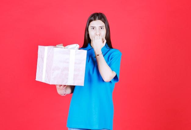 여자는 보라색 선물 상자를 들고 혼란스럽고 사려 깊은 보인다.