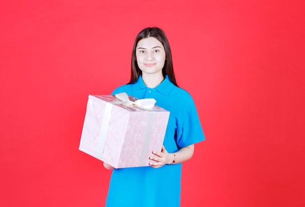 보라색 선물 상자를 들고 여자 흰색 리본으로 포장.