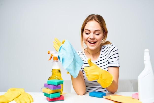 Женщина, держащая тряпку для чистки моющего средства, поставляет интерьер по дому