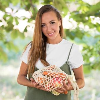 新鮮な健康食品のリサイクル可能な袋を保持している女性