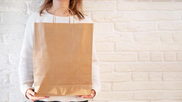 Женщина, держащая перерабатываемый бумажный пакет. идея утилизации