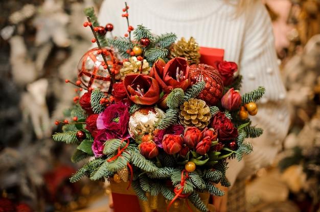 モミの木の枝で飾られたさまざまな明るい花と金のテープで赤い箱を保持している女性