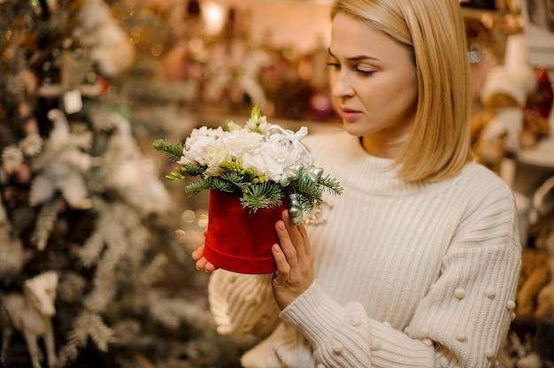 전나무 나무 가지로 장식 된 흰색 꽃과 빨간색 상자를 들고 여자