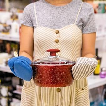 Женщина держит красную сковороду
