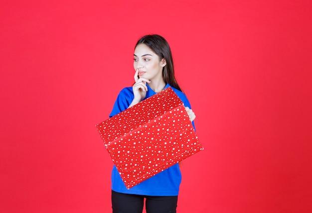 흰색 점이 있는 빨간색 선물 상자를 들고 혼란스럽고 주저하는 여자.