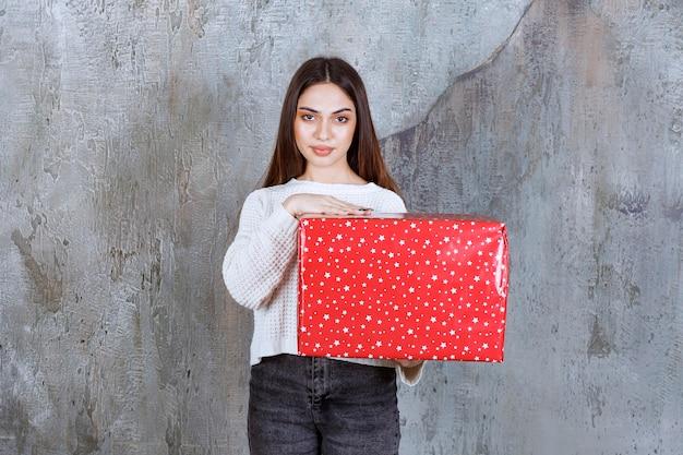 흰색 점이있는 빨간색 선물 상자를 들고 여자.