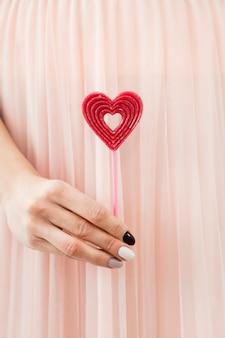 Женщина держит красное сердце на палочке