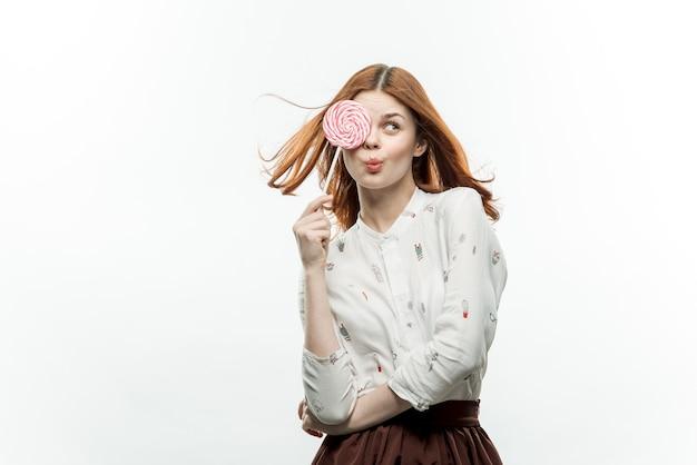 丸いロリポップを手に持った女性の感情のお菓子