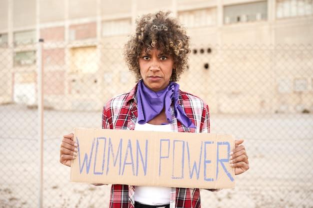 全国の女性ストライキに女性力のサインを持った女性