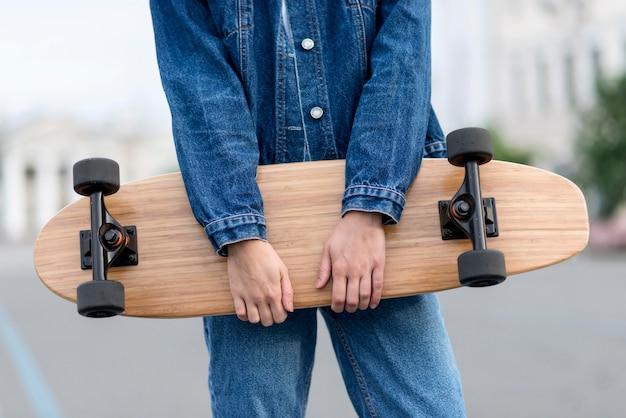 スケートボードの正面図を保持している女性