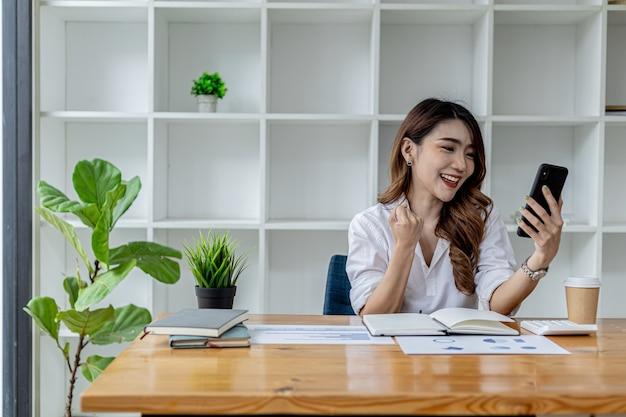 스마트폰을 들고 몸짓을 하는 여성, 지난 한 달 동안 회사의 성장하는 수입을 보고 기뻐하는 아시아 비즈니스 여성, 그녀는 성장을 관리합니다. 비즈니스 관리 개념입니다.