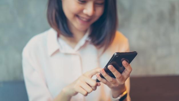 スマートフォンを保持している女性、空白の画面のモックアップ。カフェで携帯電話を使用しています。通信概念のための技術
