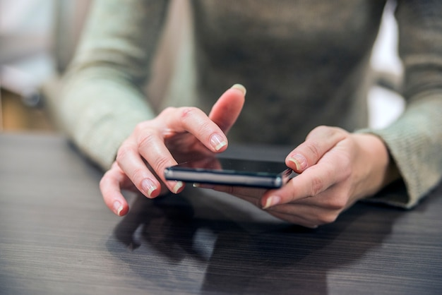 木製のテーブルにスマートフォンを持っている女性。片手で木製のテーブルに座って、女の子のクローズアップの手は、スマートフォンです。スマートフォンでインターネットをサーフィンするビジネスマン。