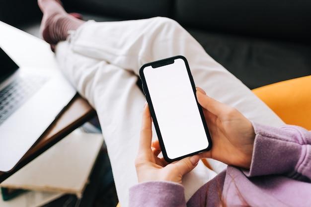 여자는 흰색 화면이있는 스마트 폰을 모의, 집에서 거실의 안락 의자에 쉬고 있습니다.